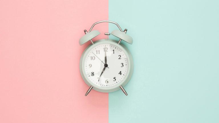 Pastellfarbene Uhr vor pink-grünem Hintergrund