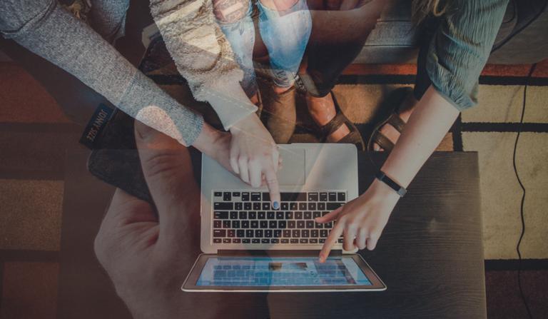 Personen deuten auf einen Laptop mit transparentem Bild einer Geldbörse im Hintergrund